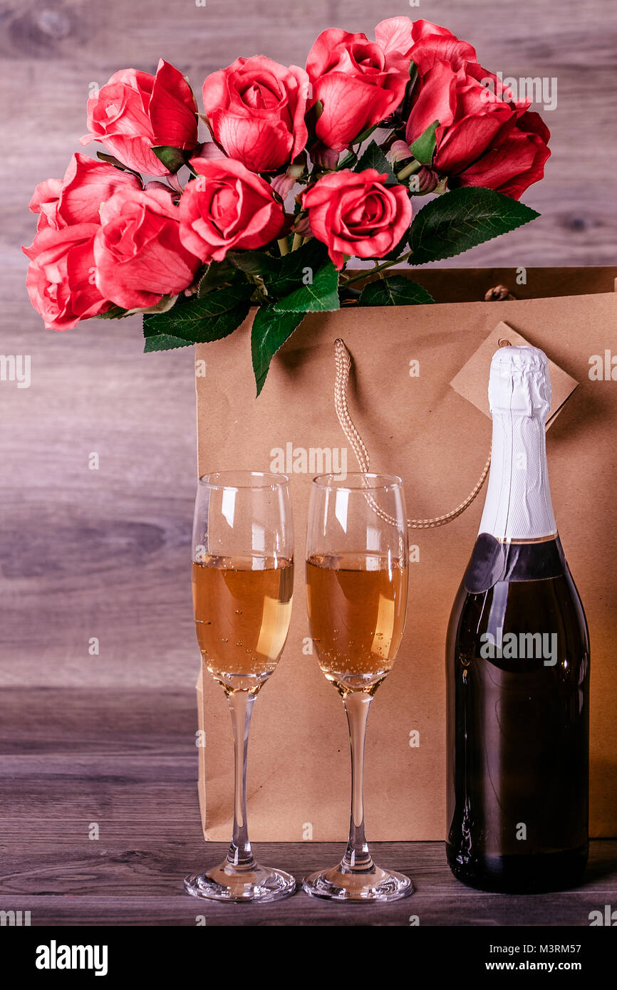 Valentines Day Champagne Wine Glasses And Red Roses In A Paper Bag