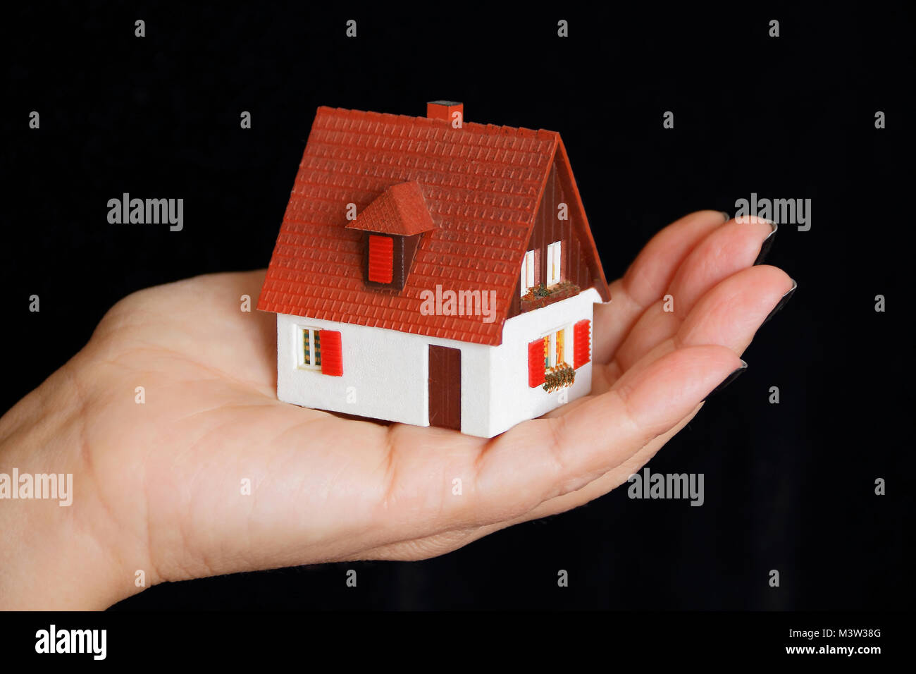 Image Of Dollhouse In Human Hand On Black Background Stock Photo