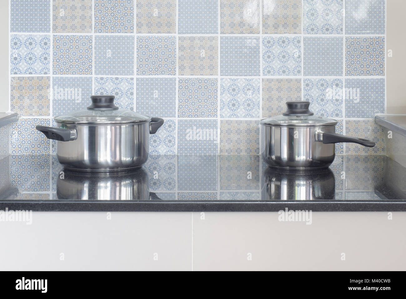 Stainless steel pots on electric hob in the kitchen Stock Photo ...