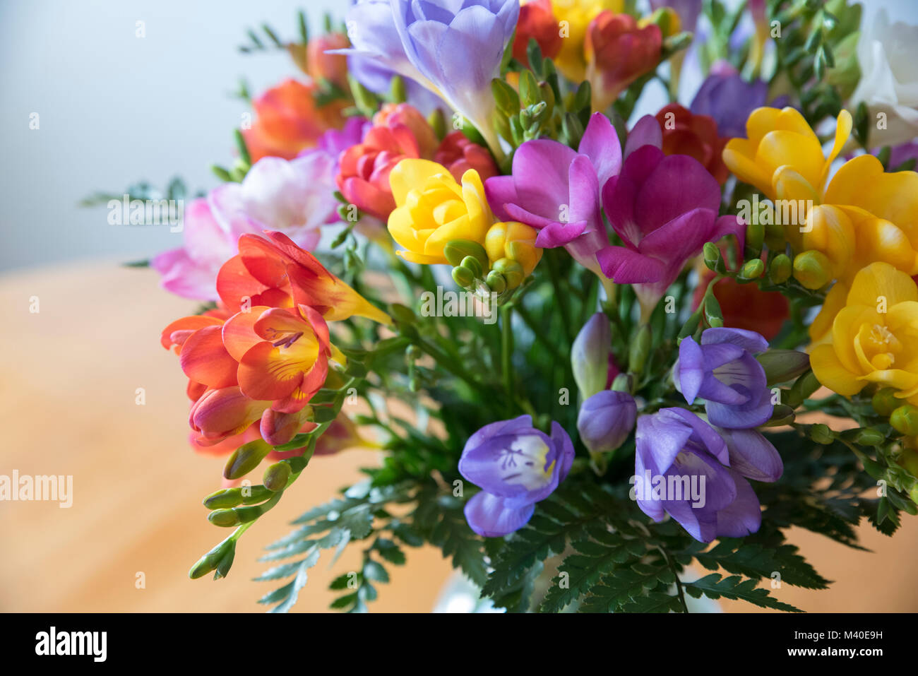 Colorful flower bouquet in a glass bowl on a wooden table Stock ...