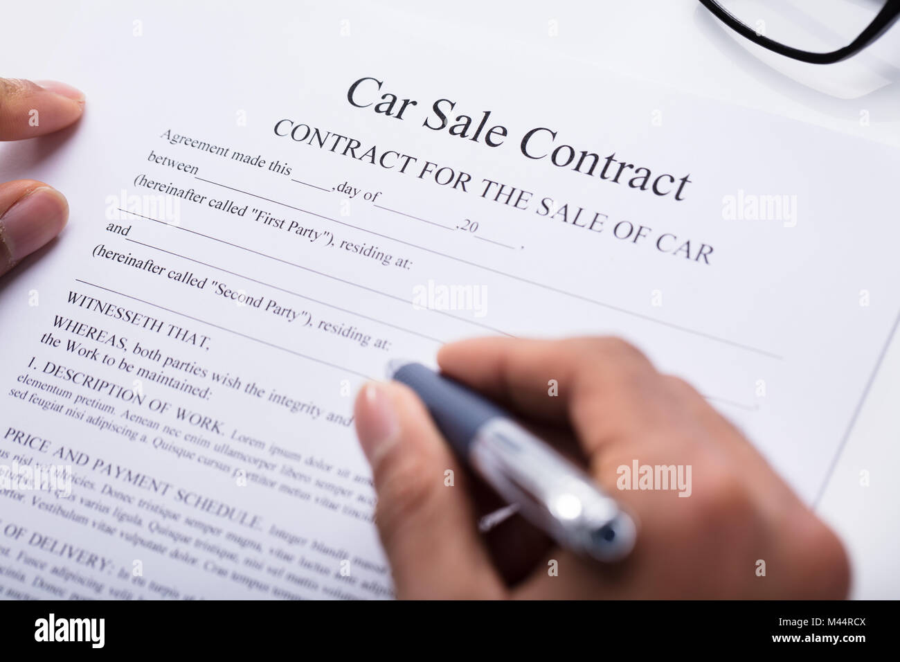 close up of a persons hand filling car sale contract form