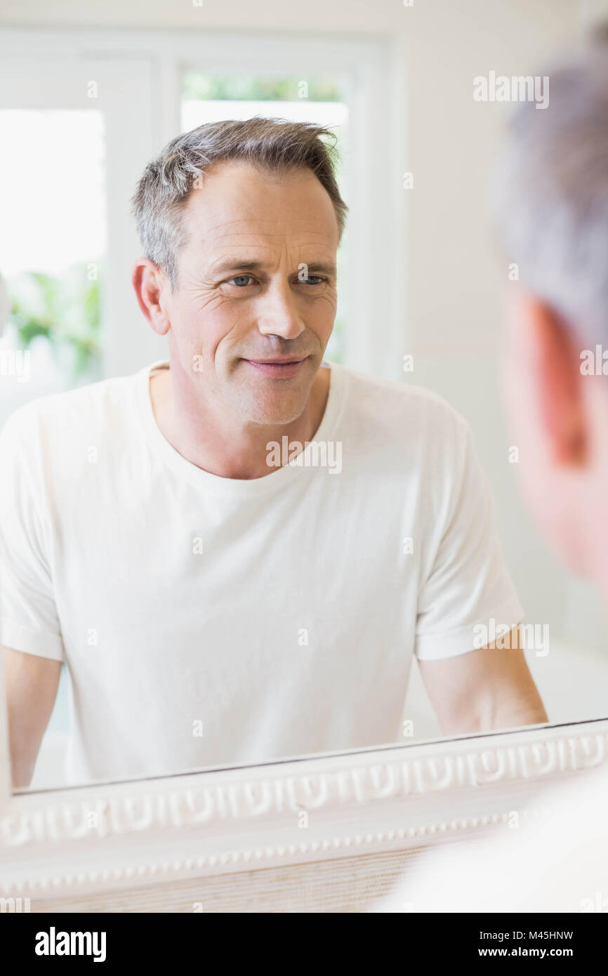 handsome man looking at himself in the mirror stock photo 174686005