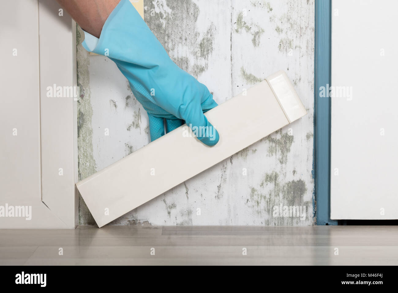 Close-up Of A Person Hand Placing Tiles On Moldy Wall At Home Stock ...