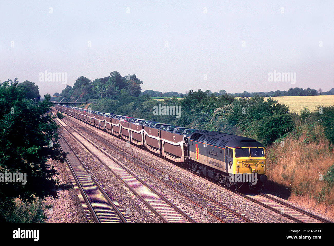 A class 47 diesel locomotive number 47241 working a loaded car train at  Shottesbrooke in Berkshire on the 20th July 1996.
