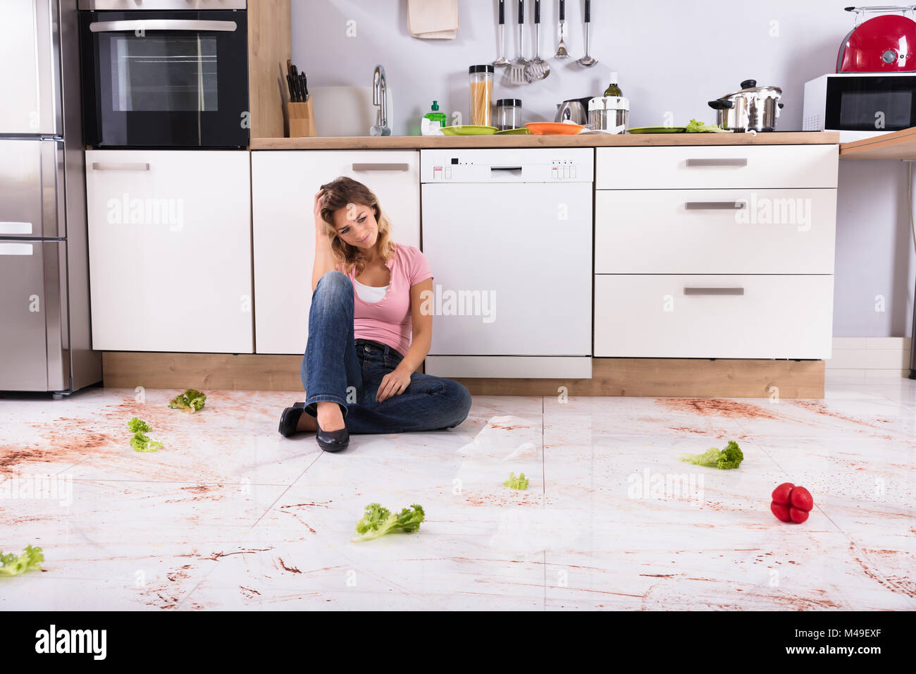 Unhappy Young Woman Sitting On Dirty Kitchen Floor At Home Stock ...