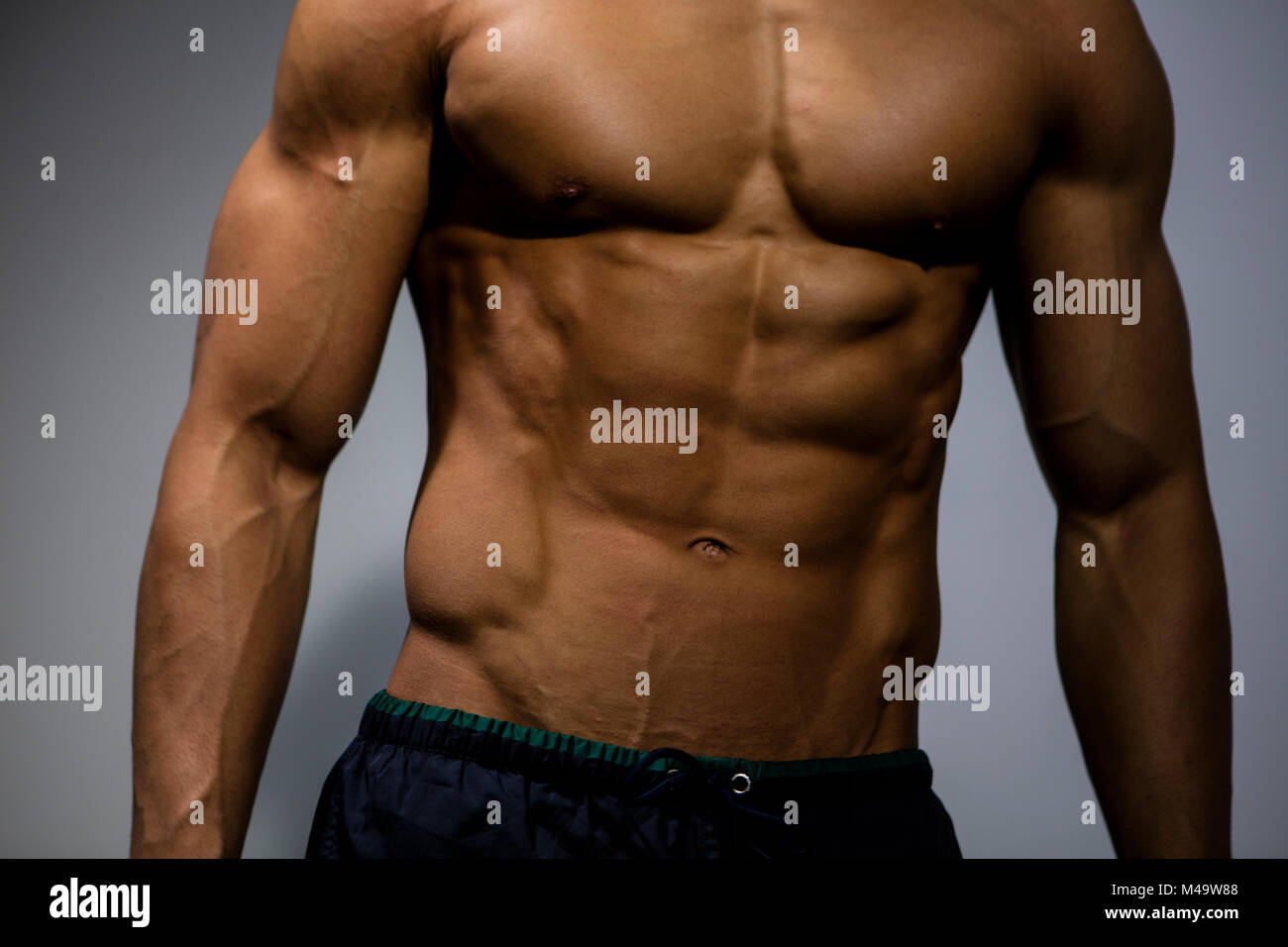 The Muscular Torso Of A Fitness Model Front Facing Stock Photo