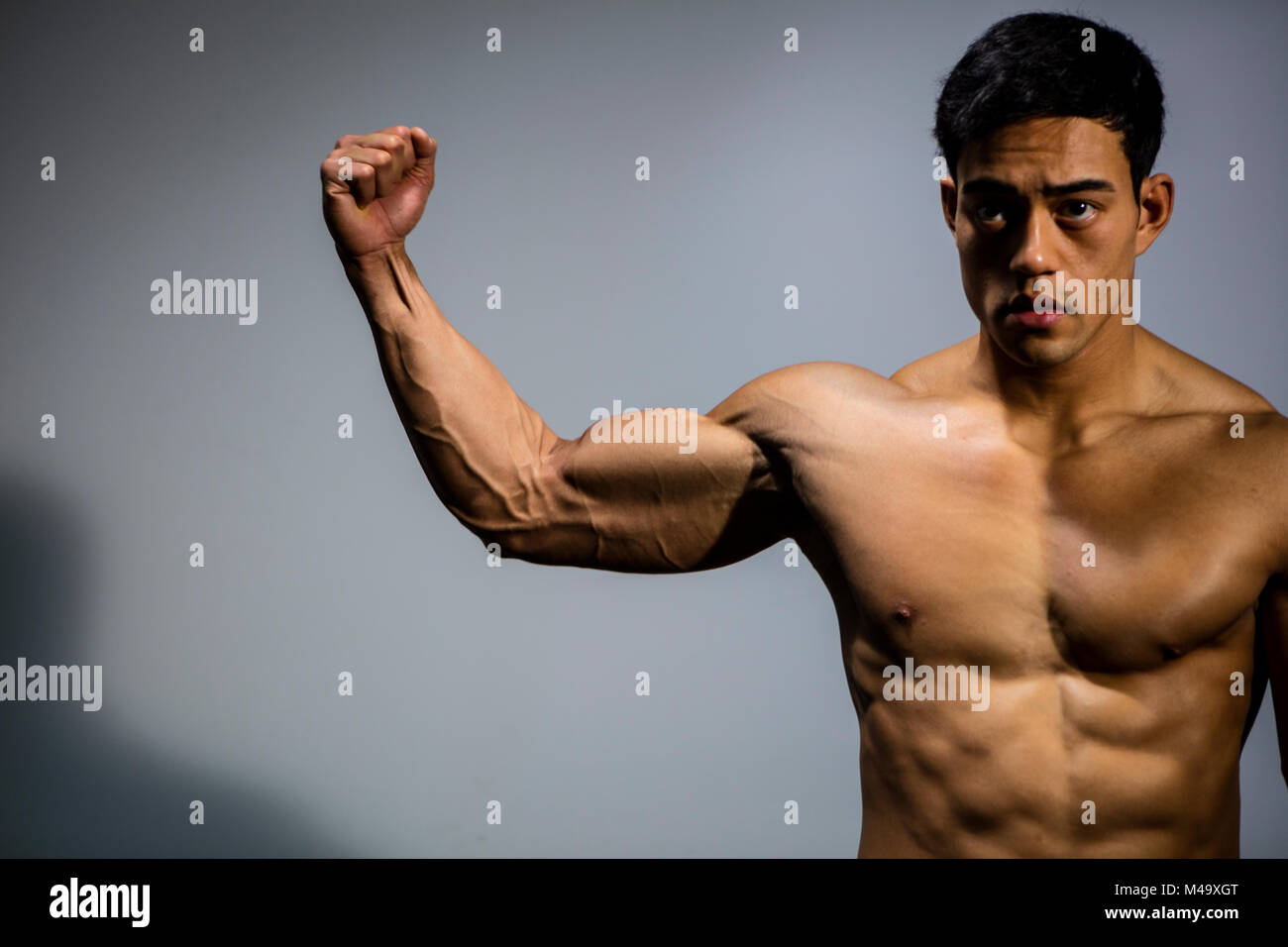 An Asian Fitness Model Flexing His Bicep Muscle Front Facing Stock