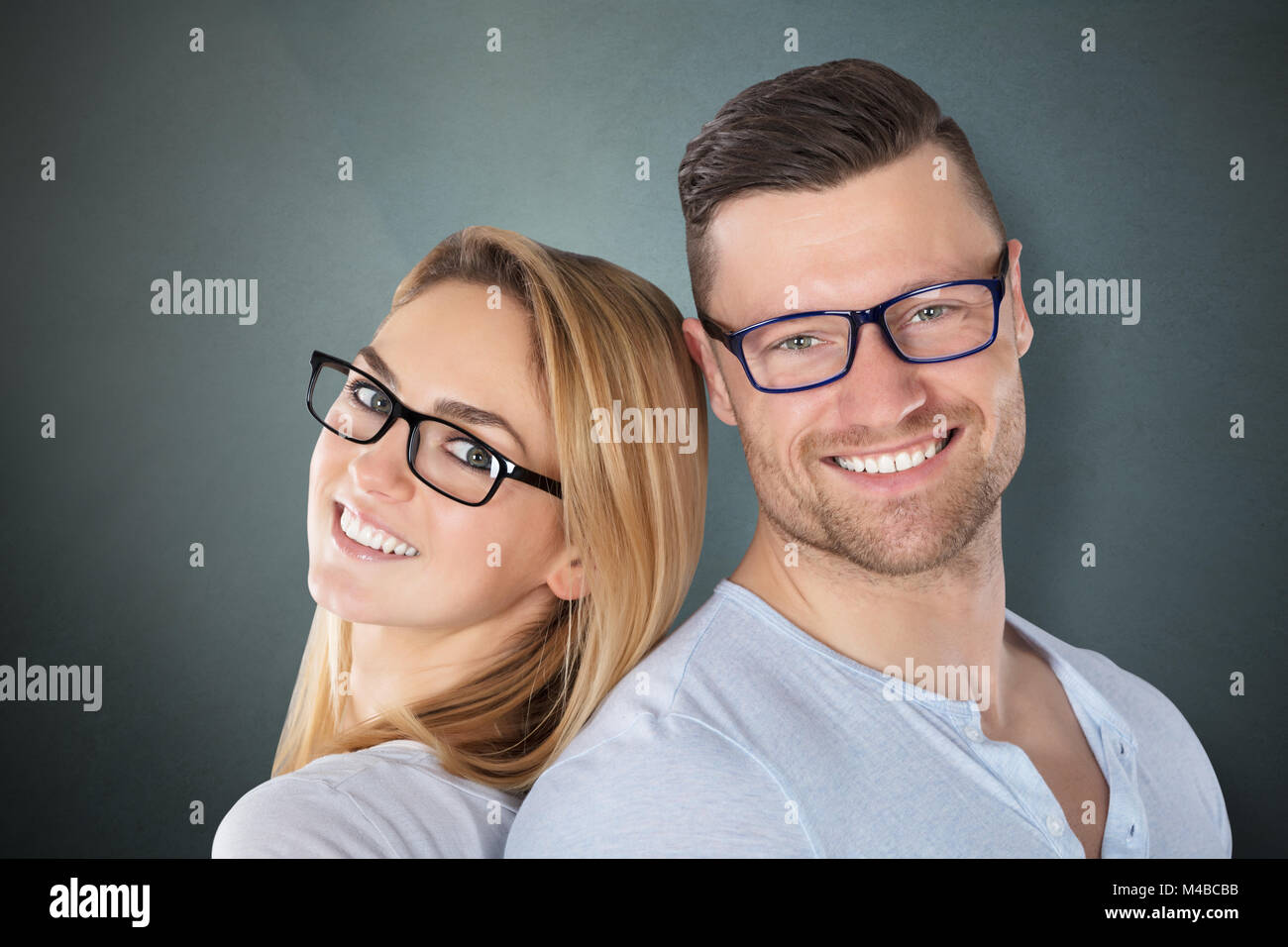 a2d538d232 Happy Young Couple With Stylish Eyeglasses Against Grey Background ...