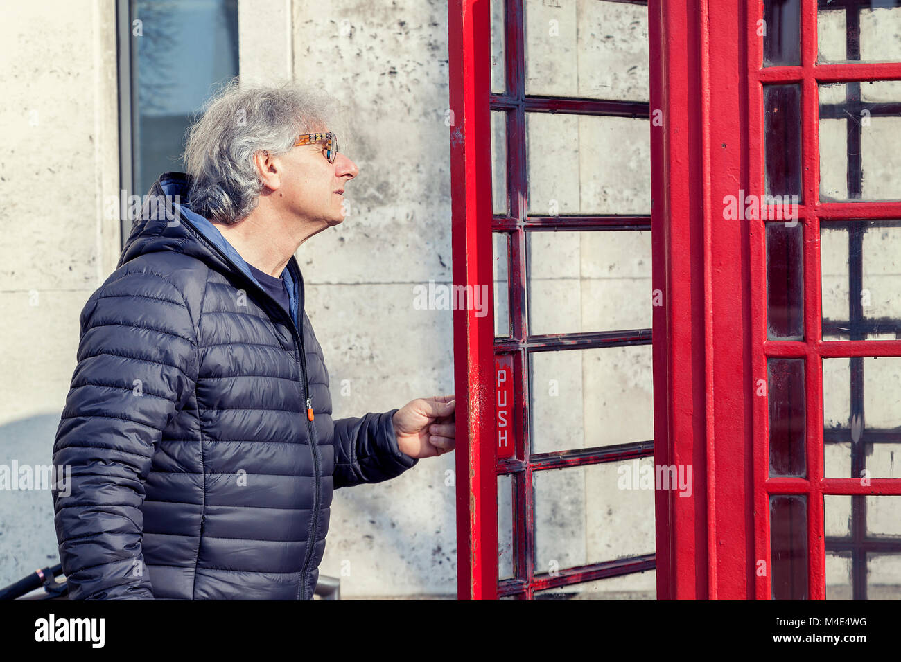 Mature man walks into a red telephone box in london stock photo mature man walks into a red telephone box in london planetlyrics Choice Image