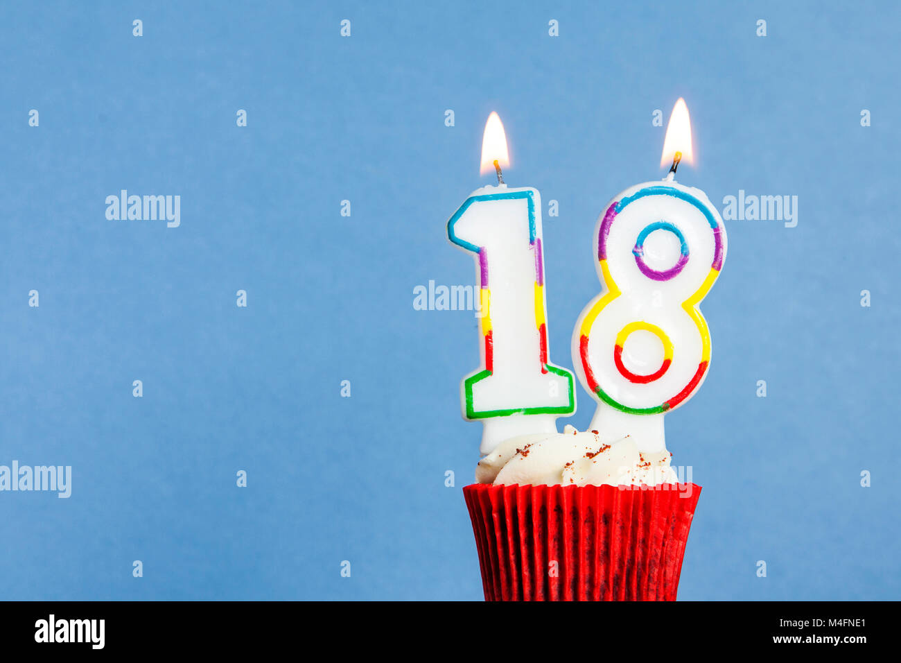 Number 18 Birthday Candle In A Cupcake Against Blue Background