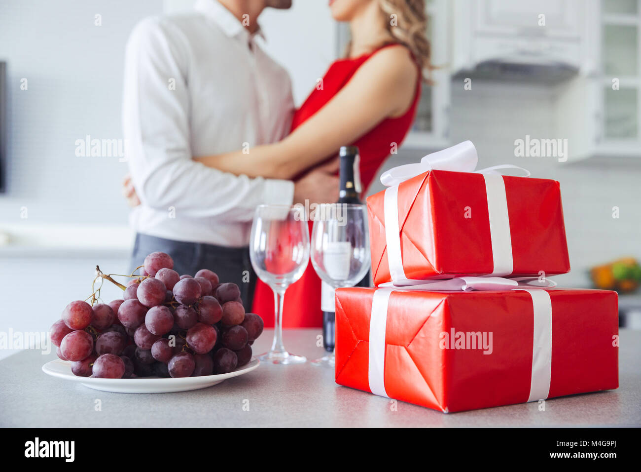 Close up shot of pretty gift boxes bottle of wine and grape on close up shot of pretty gift boxes bottle of wine and grape on table lovers hugging in the background negle Images