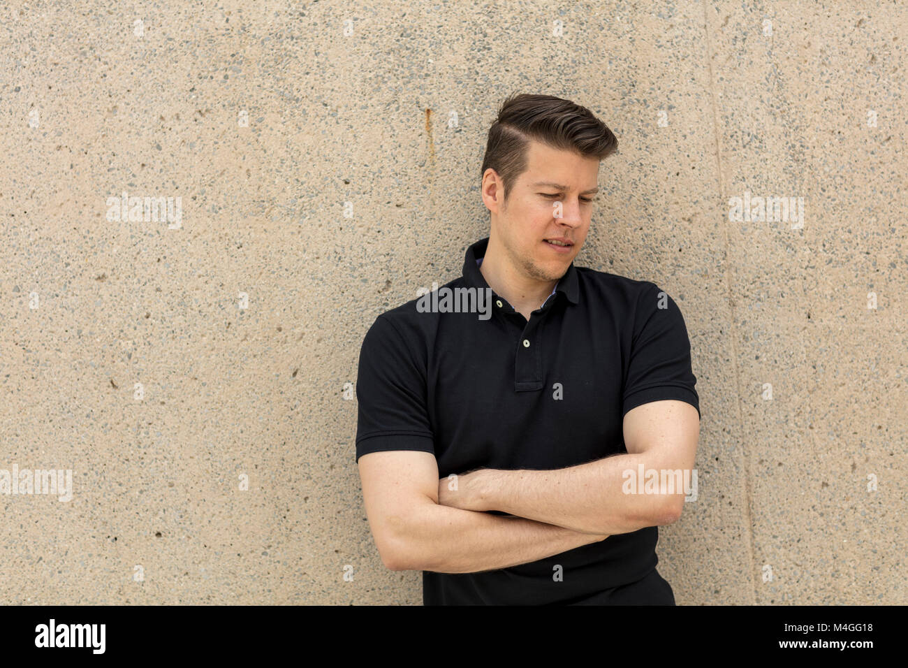 handsome man portrait pose in front on an outdoor beige wall on a