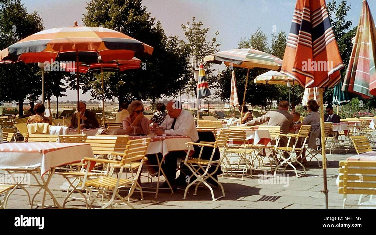 Guests sit at tables in a garden restaurant at the airport Riem ...
