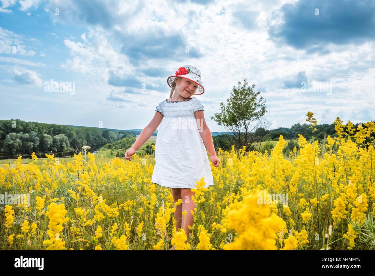 Cute Little Laughing Girl Walking In Field Of Yellow Flowers Stock