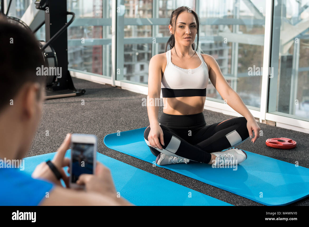 3d38d16e09930 Full length portrait of fit young woman posing for photo during yoga  practice in modern health club