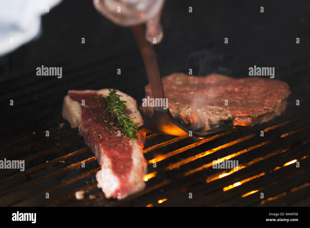 preparing meat on the grill, chef flips the piece with shovel stock