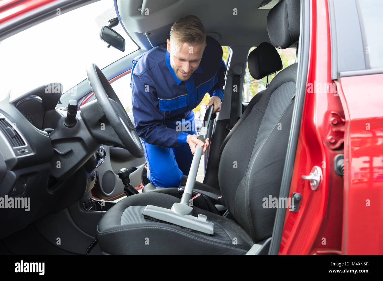 Young Happy Worker Vacuuming Car Seat With Vacuum Cleaner Stock