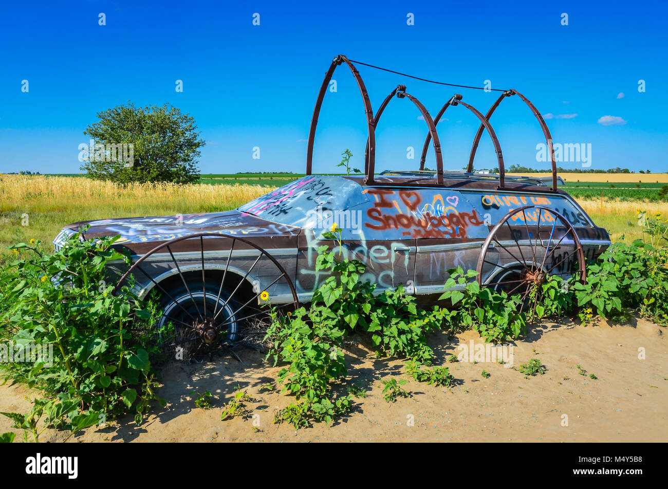 Solo Station Wagon Covered In Wagon Wheels Forms Trellis For Plants