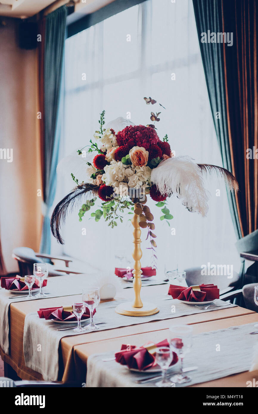 decor of a wedding restaurant in maroon color with flowers stock