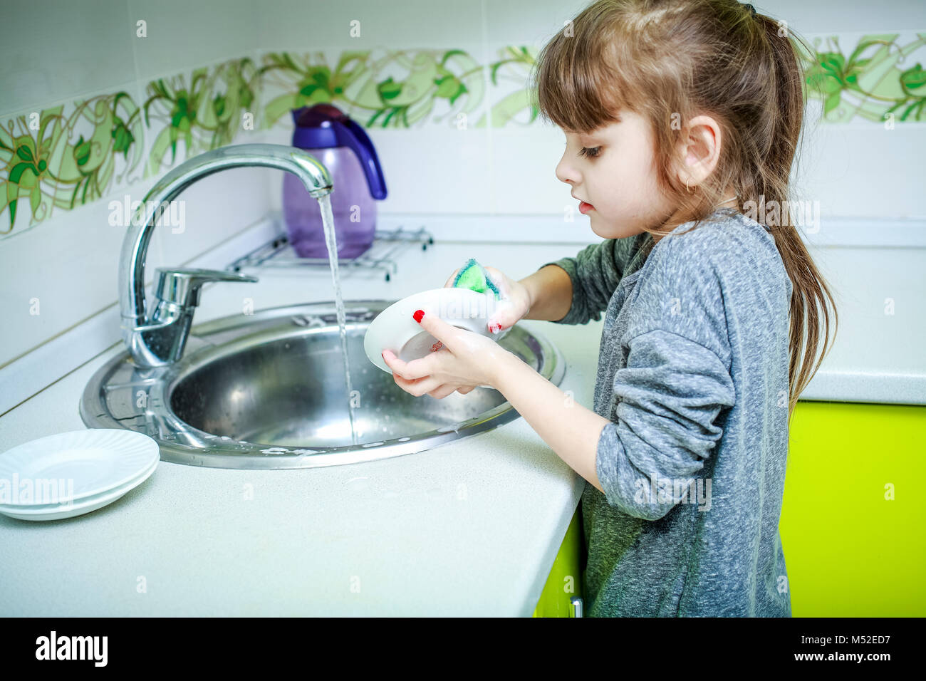 A little girl stands on a chair and carefully washes dishes in the ...