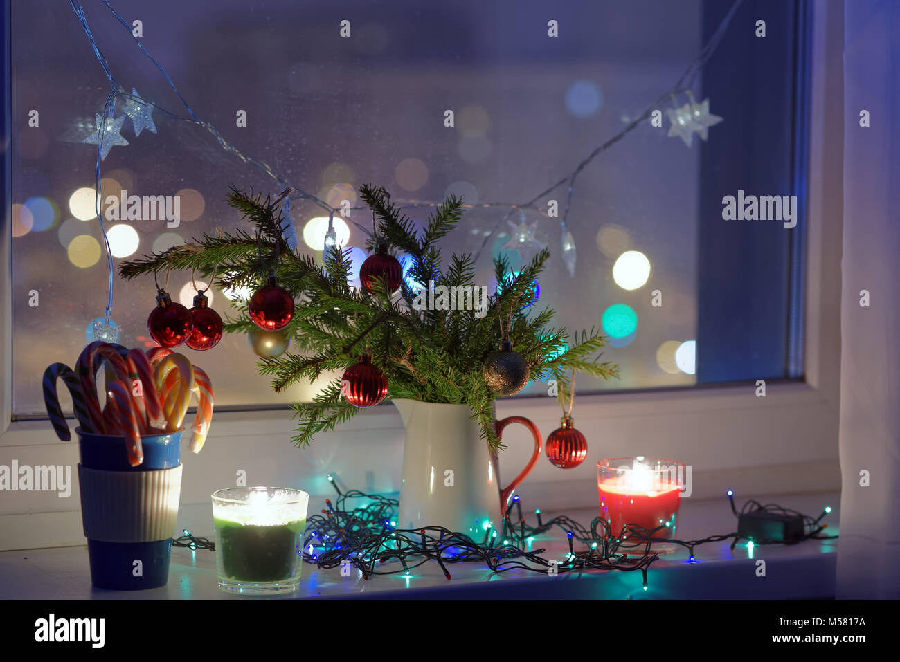 christmas decorations and candles on a window sill