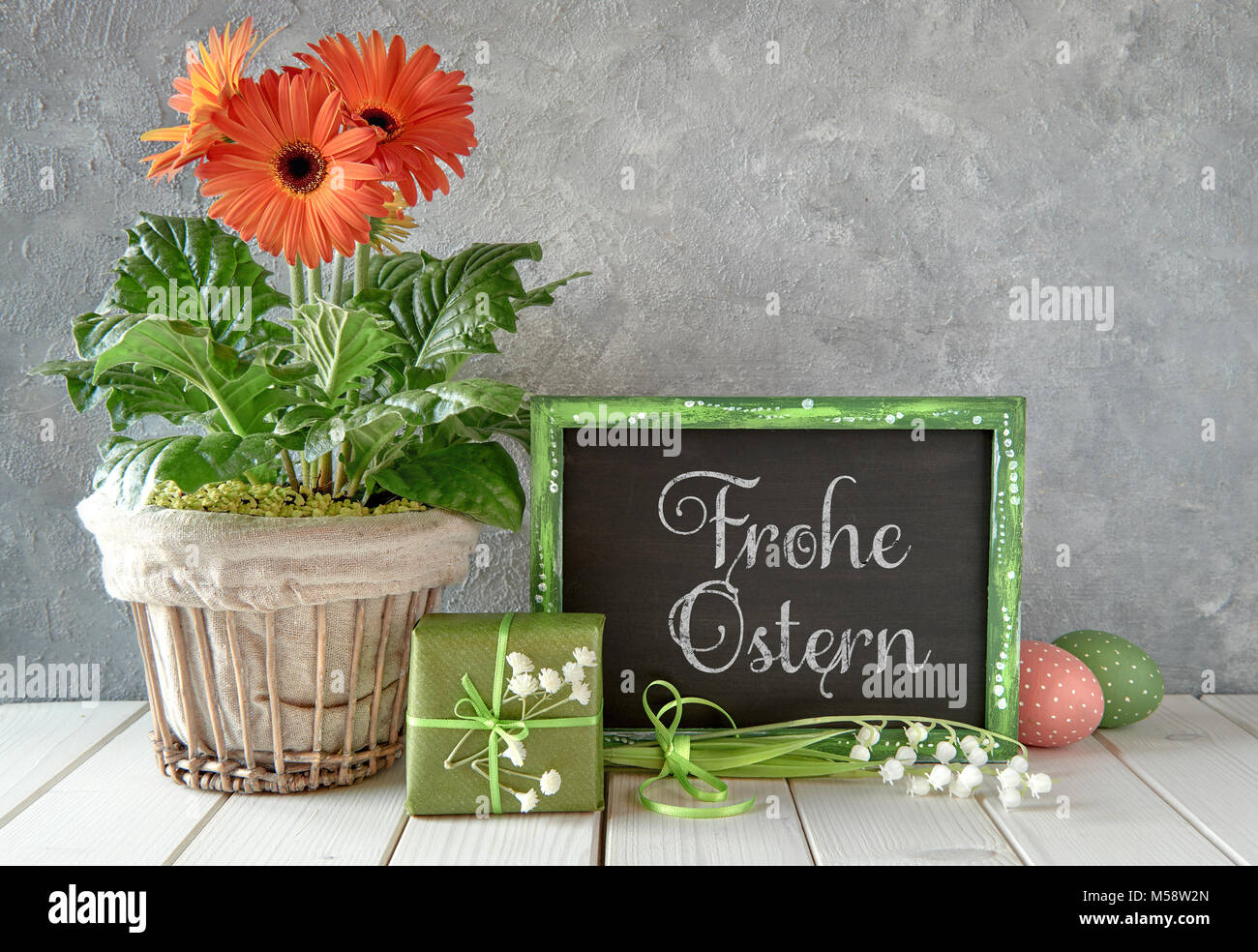 Spring flowers easter decorations and a blackboard on white table spring flowers easter decorations and a blackboard on white table text frohe ostern that means happy easter in english on a blackboard mightylinksfo