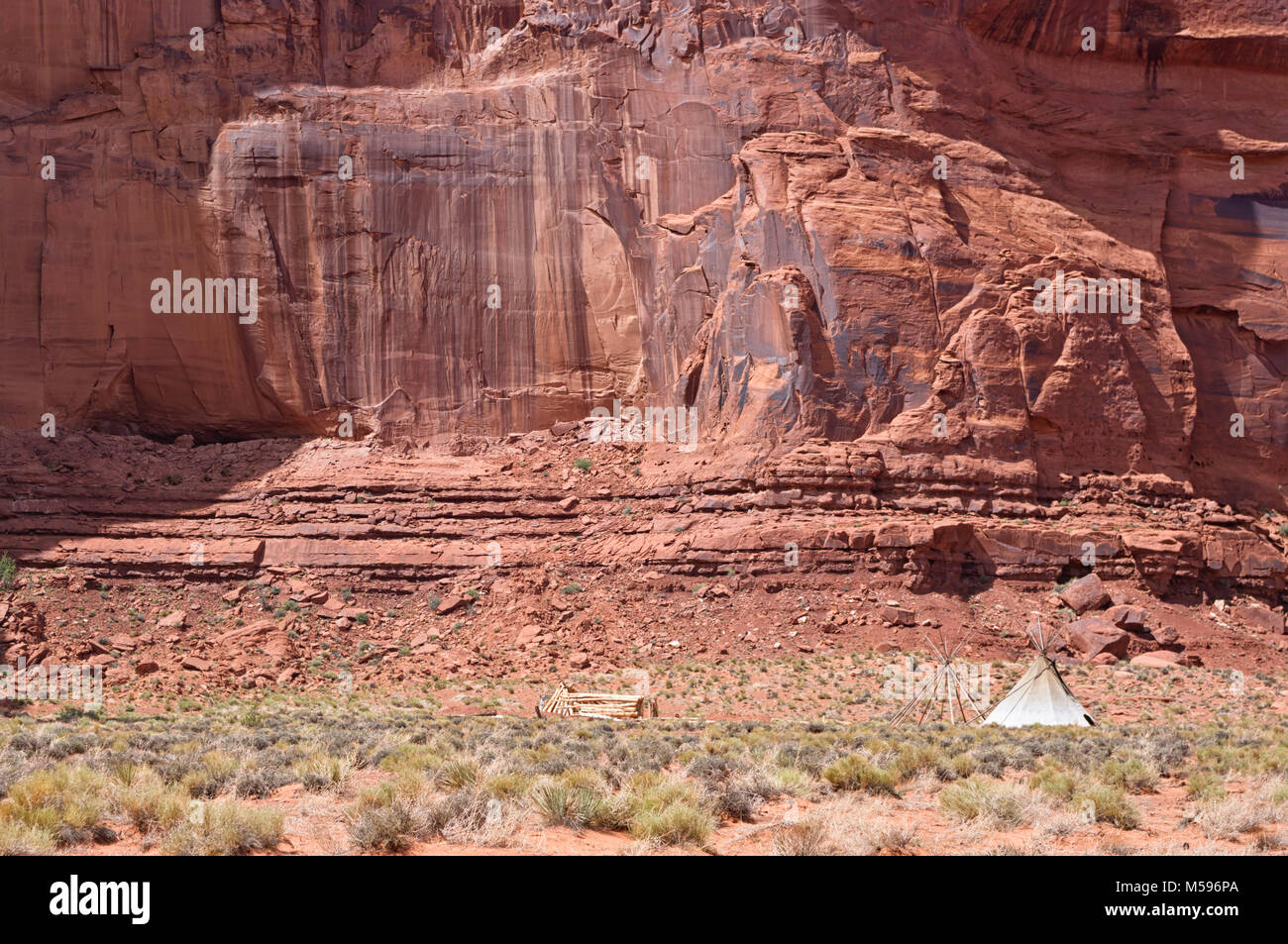 Indians tent in front of a red rock cliff in a remote spot in the famous Monument Valley USA. Navajo traditional c& in the desert. Concept for adve & Indians tent in front of a red rock cliff in a remote spot in the ...