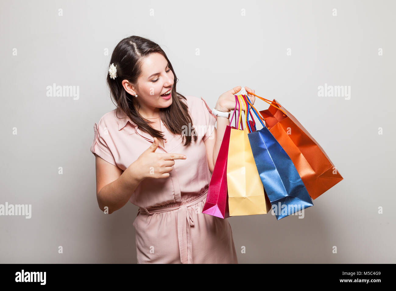 Modern Teenager In A Dress Holds Gift Bags From Her Birthday Party