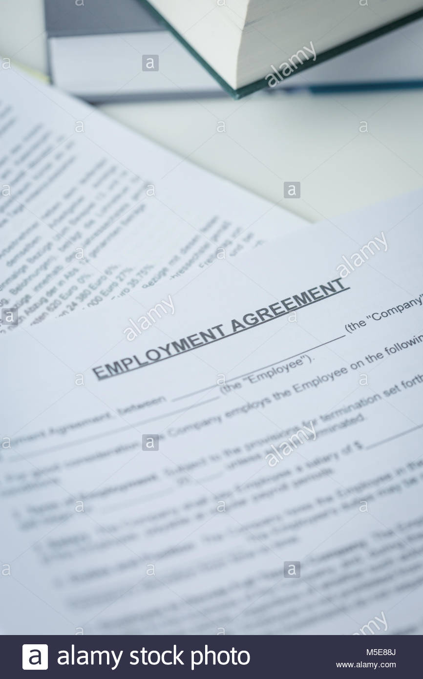 Agreement Of Employment With Pen And Laptop Lying On A Desk In A