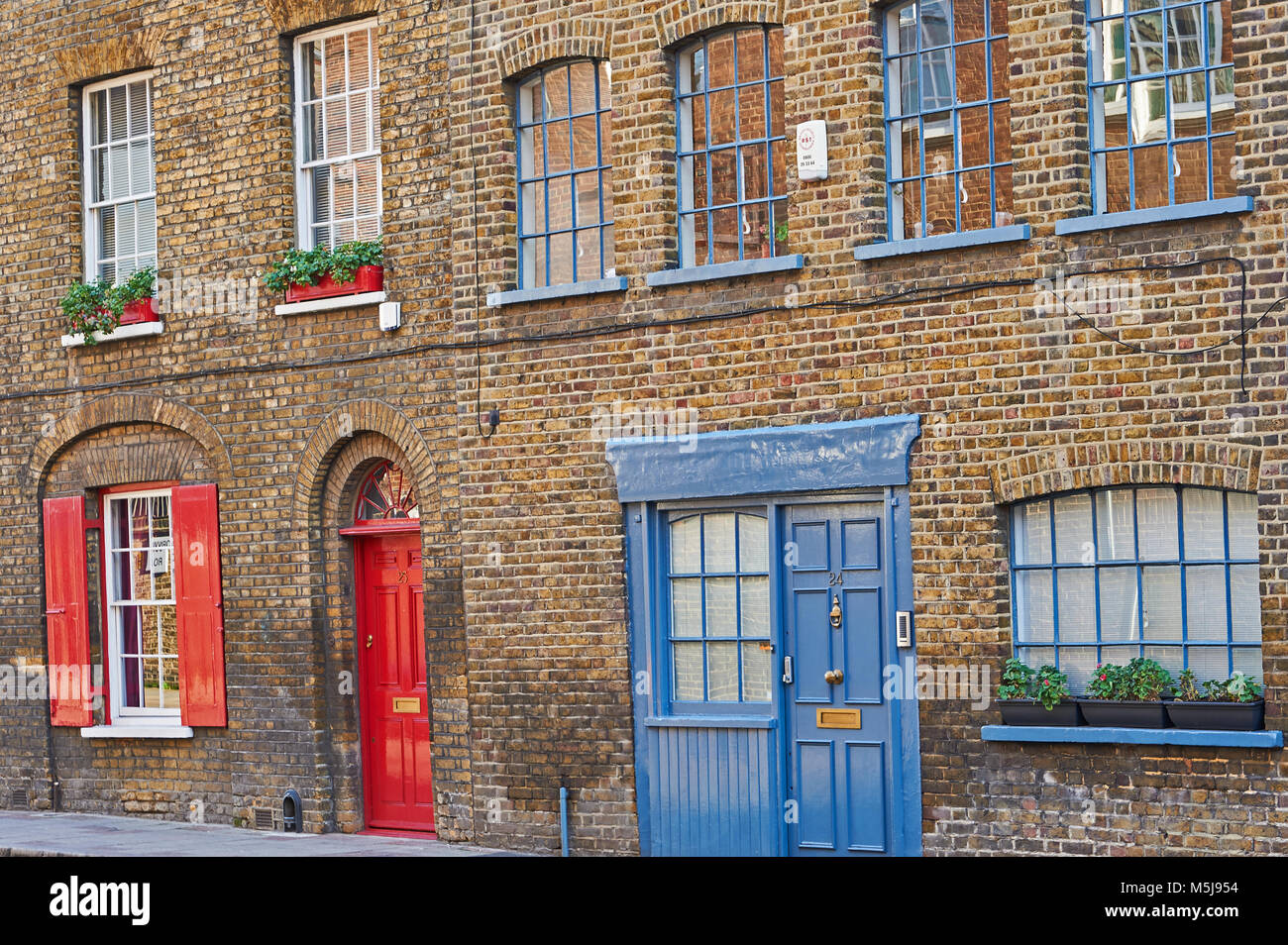 A Pretty Row Of Brick Terraced House With Red And Blue Doors Red