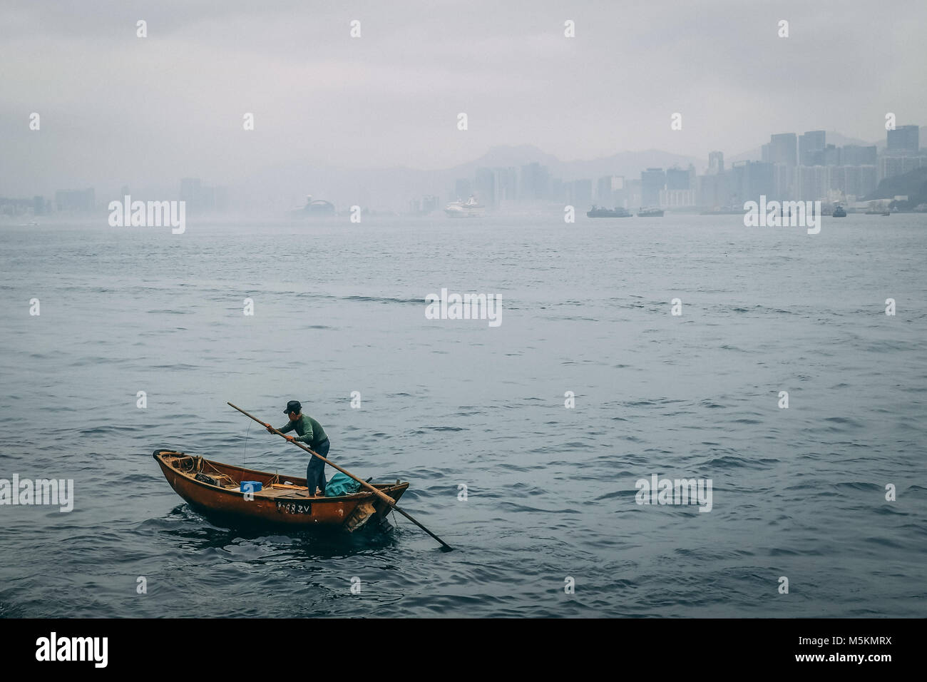 A Lone Fisherman Is Fishing In Wooden Paddle Boat Hong Kong