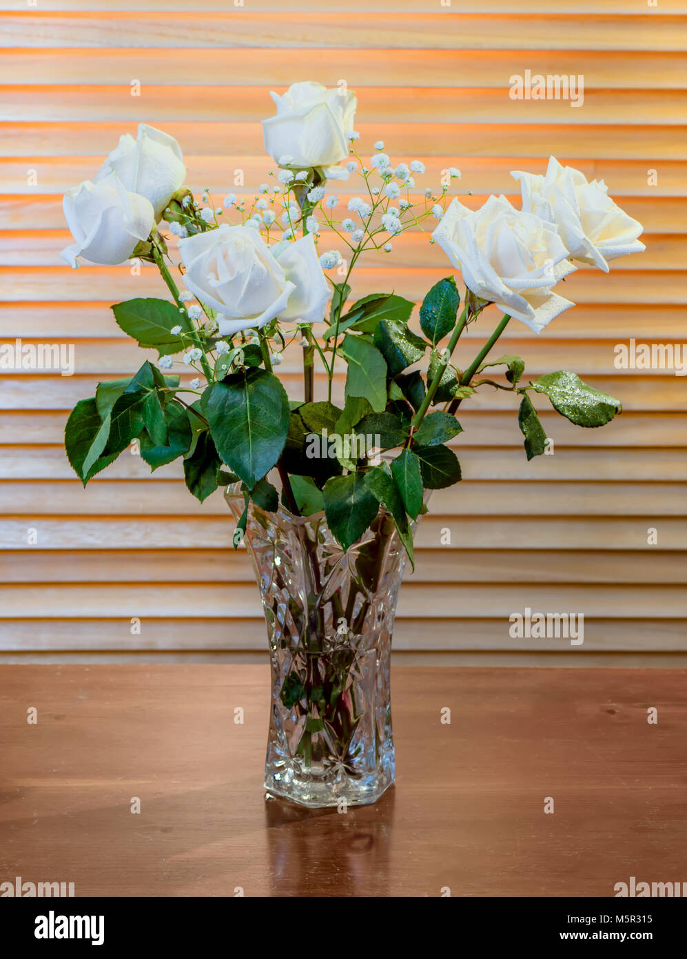 The Plant Is A Bouquet Of White Roses With Green Leaves And Small