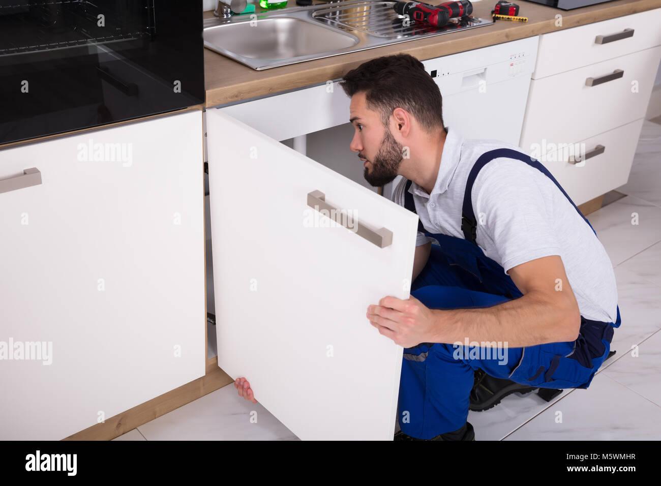 Young Handyman Fixing Sink Door In Kitchen Stock Photo: 175741939 ...