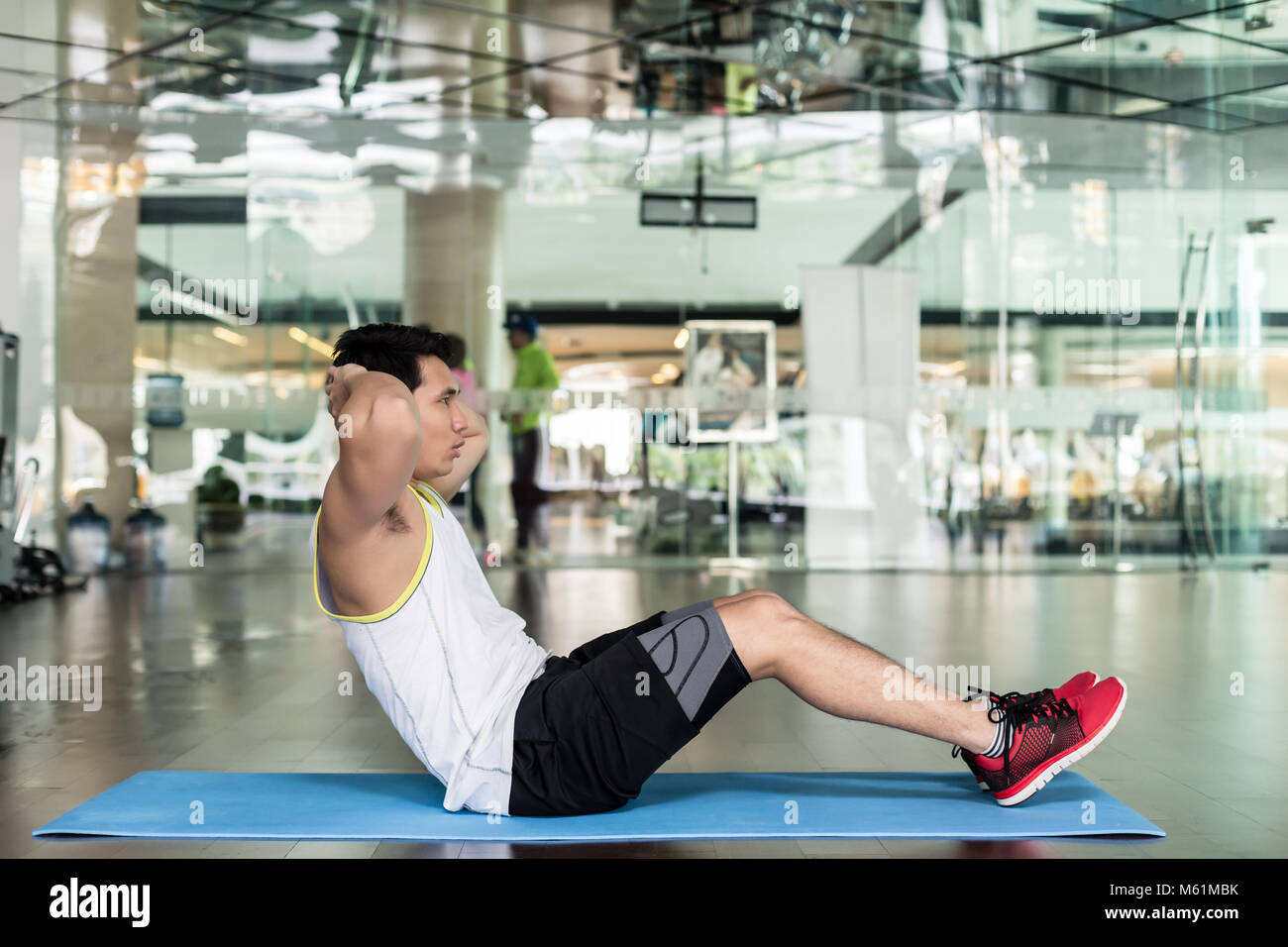 Young Man Sitting Down While Doing Crunches For The Abdominal