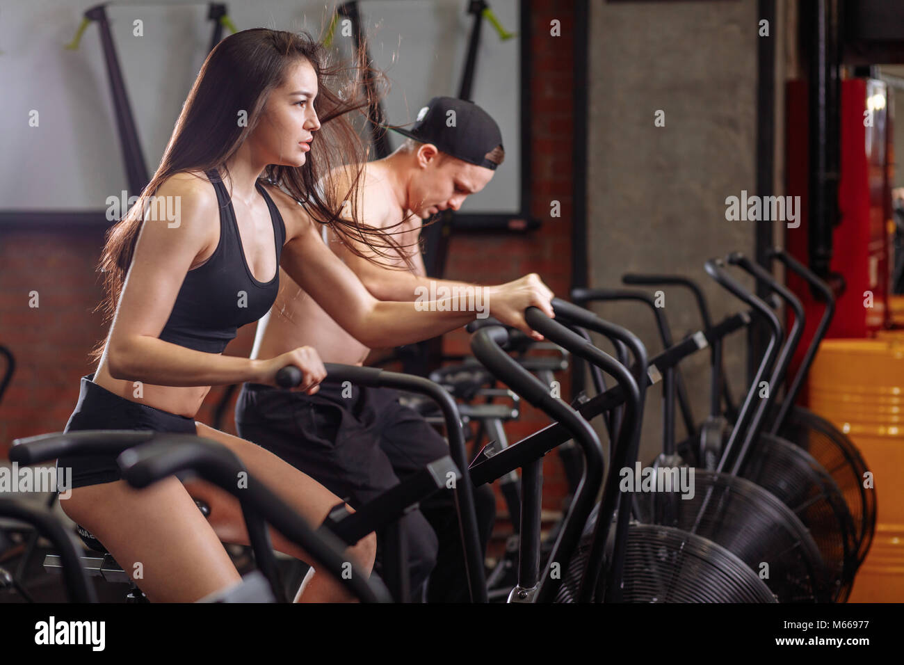 Woman And Man Biking In Gym Exercising Legs Doing Cardio Workout Cycling Bikes