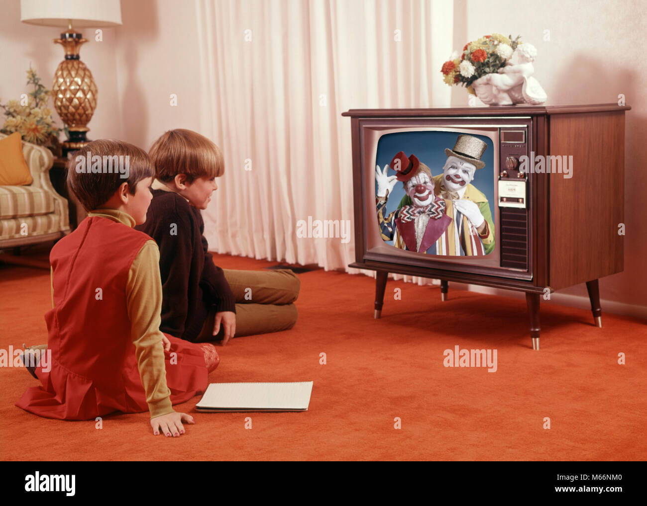 1960s two children boy girl sitting red carpet living room watching