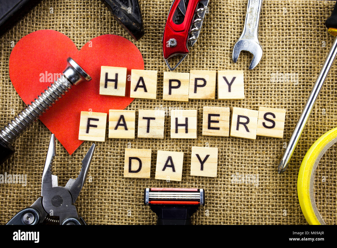 happy fathers day message on a hessian jute background with frame of tools and ties