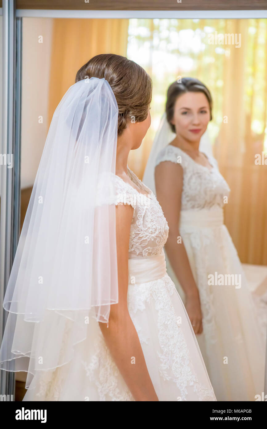 Beautiful young bride in wedding dress looking in mirror Stock Photo ...