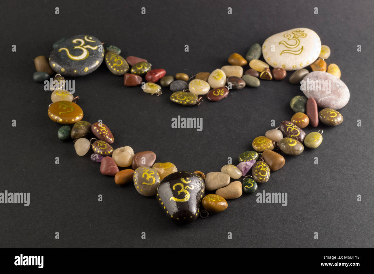 Om symbol stock photos om symbol stock images alamy heart shaped pile of stones painted with om symbol stock image biocorpaavc Image collections