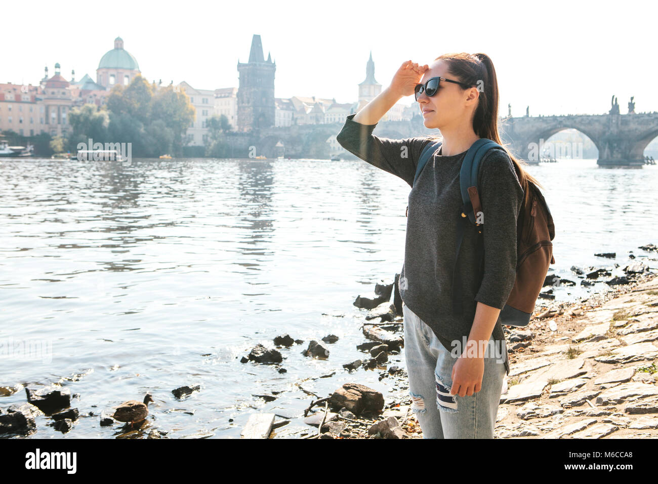 3b5f87926545 A beautiful young tourist girl with a backpack stands next to the river  Vltava in Prague and admires the architecture of the city.