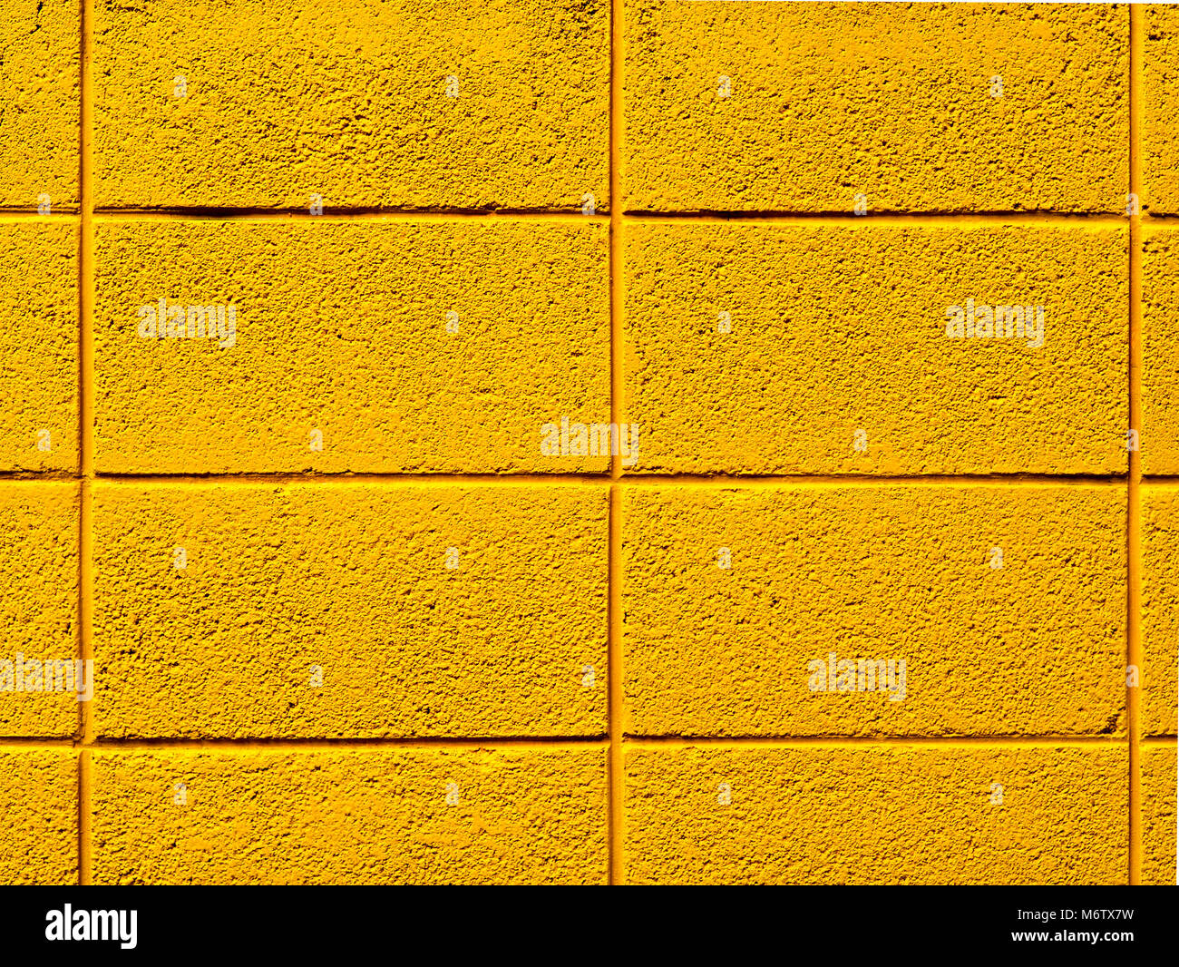 Bright yellow painted cinder block wall background photograph Stock ...