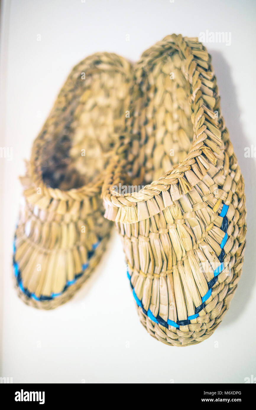 Bast shoes decoration hanging on the white wall Stock Photo ...
