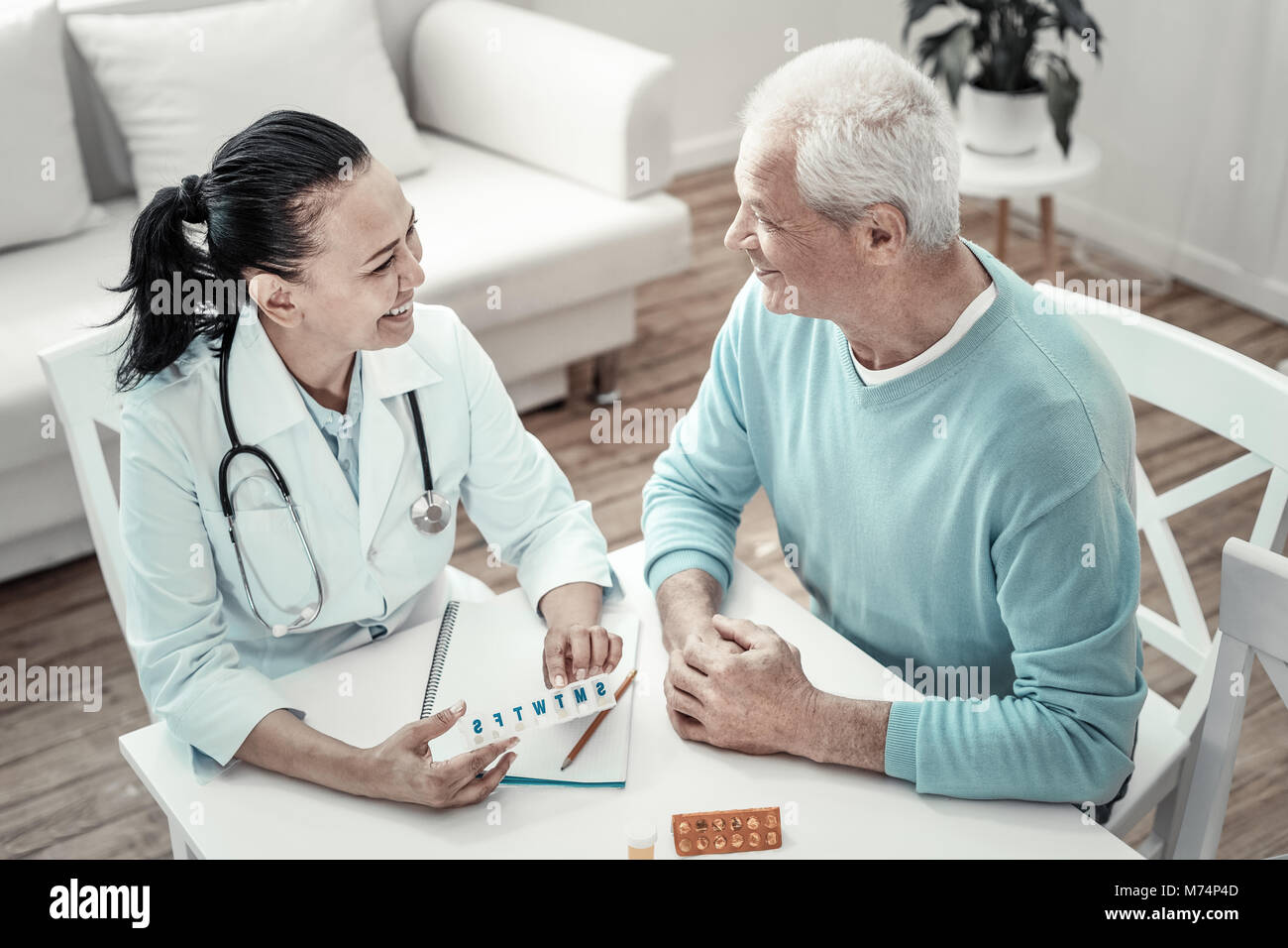 mature cute nurse giving pills to the patient and smiling stock