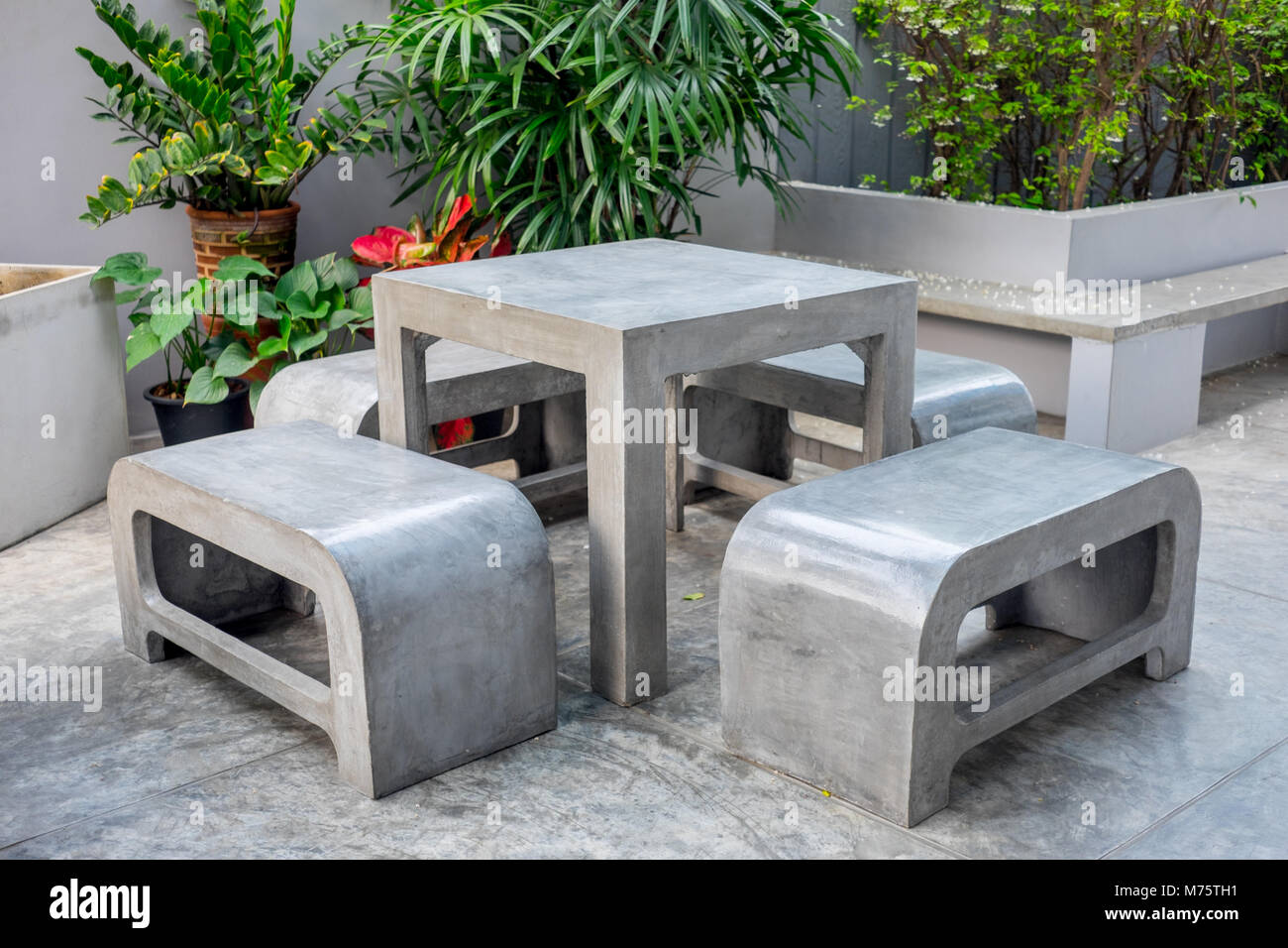 Concrete Outdoor Furniture Set In The Small Garden Including On Table And  Four Benches