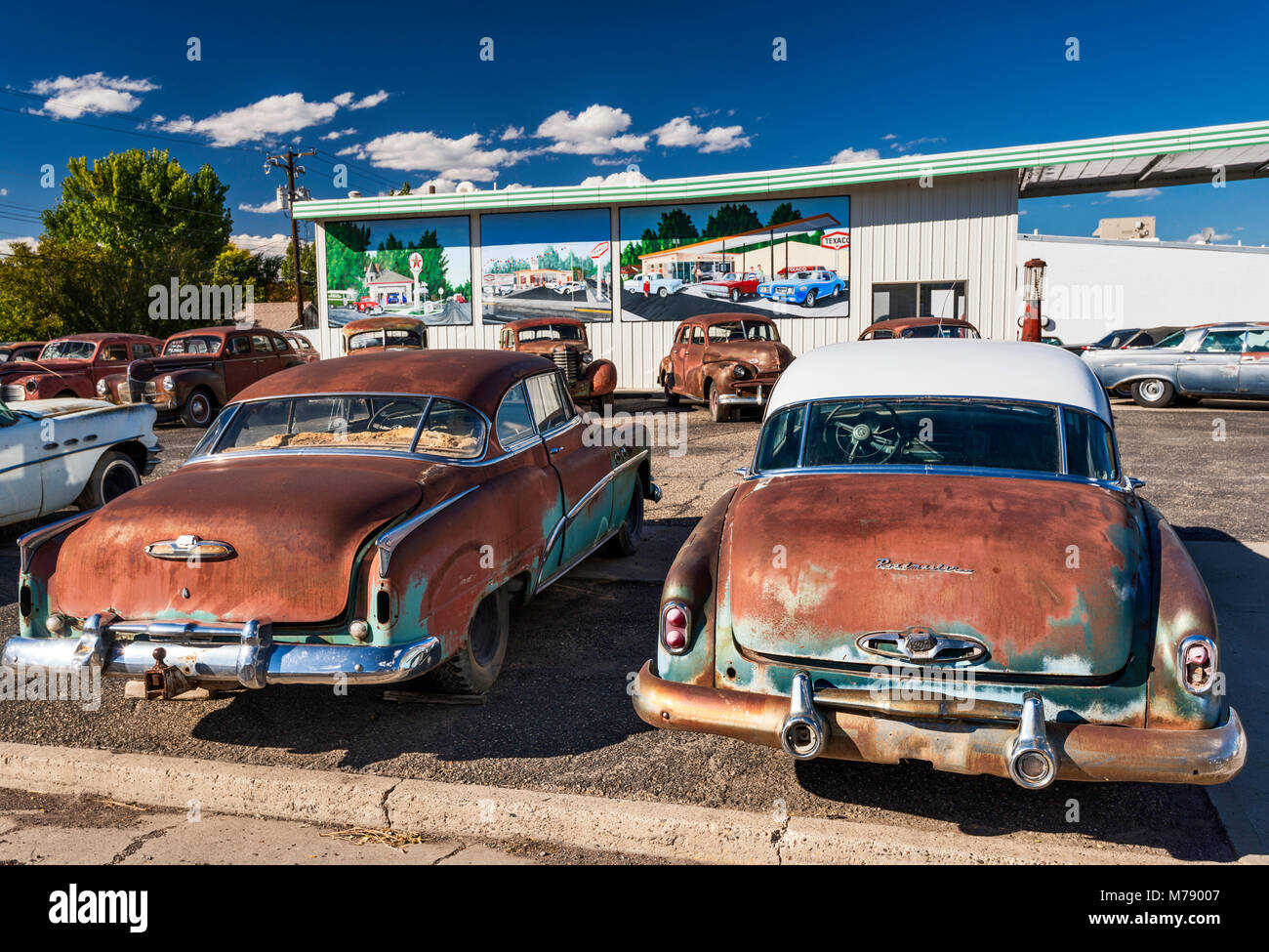Old, rusted cars for sale, murals behind on wall of service station ...