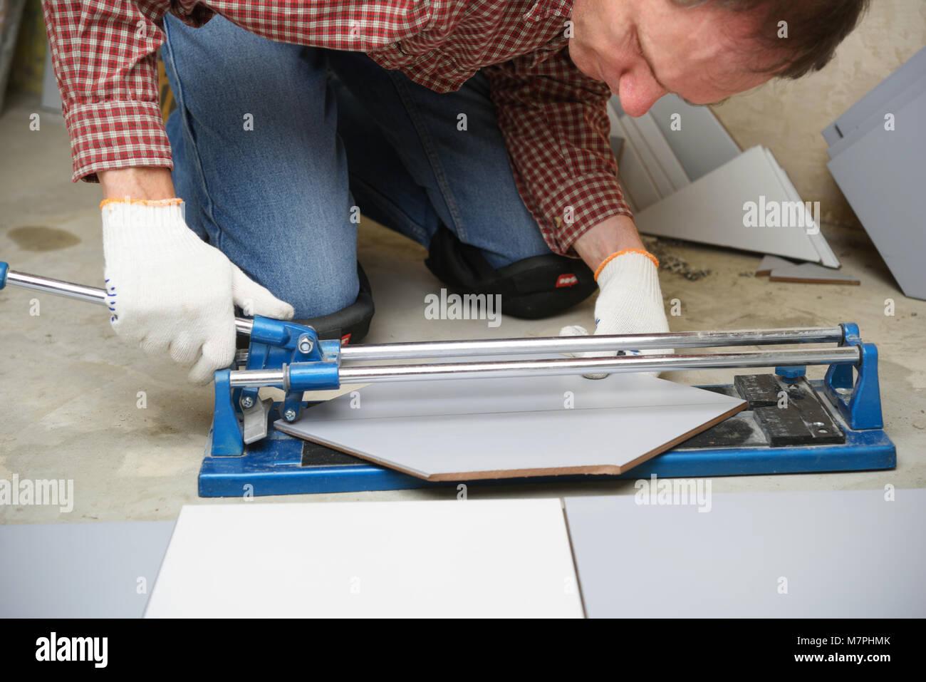 Tiler cutting ceramic tiles during floor installation stock photo tiler cutting ceramic tiles during floor installation dailygadgetfo Gallery