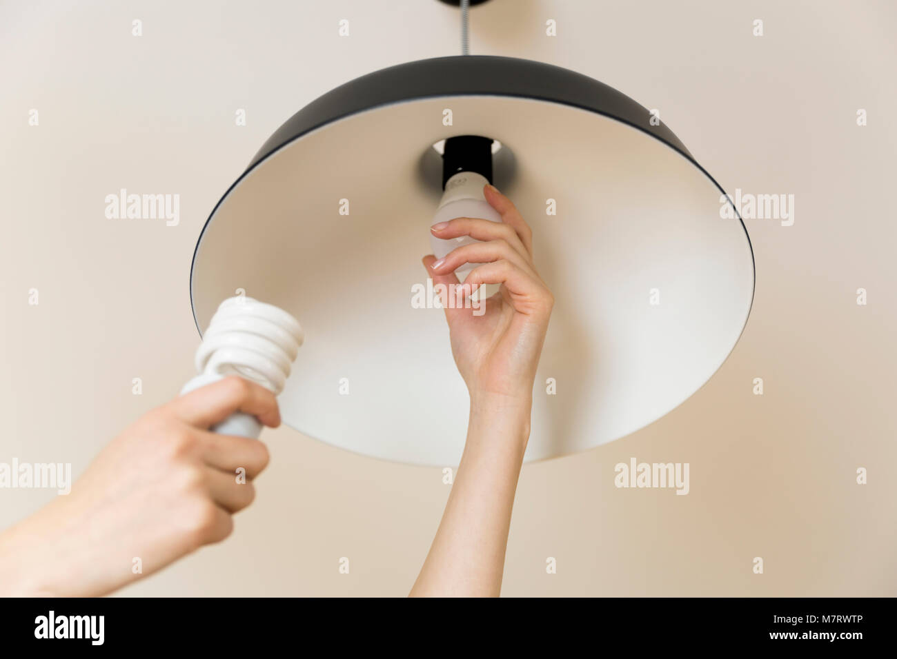 Woman replacing light bulb at home. Power save LED lamp changing ...