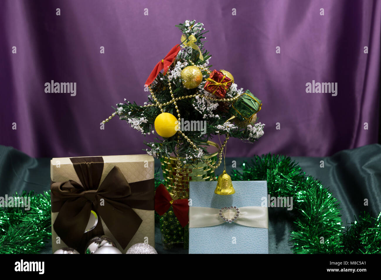 giftboxes pink and white christmas decorations balls hanging on a decorative white christmas tree concept new year celebration background