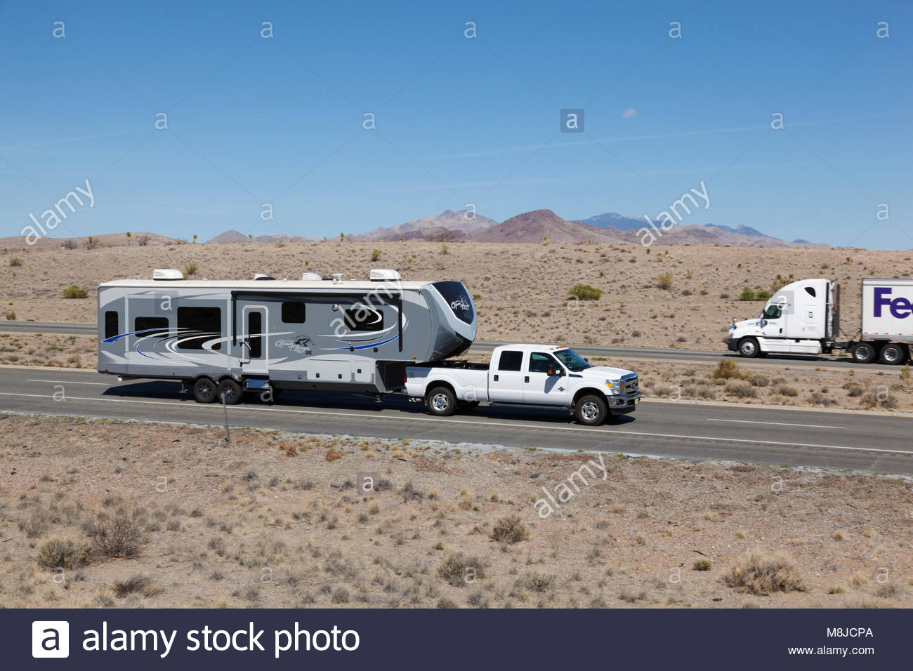 Pickup Truck Pulling Travel Trailer Fifth Wheel On Interstate Highway In Southeastern Arizona USA Driver And Passenger Barely Visible Cab