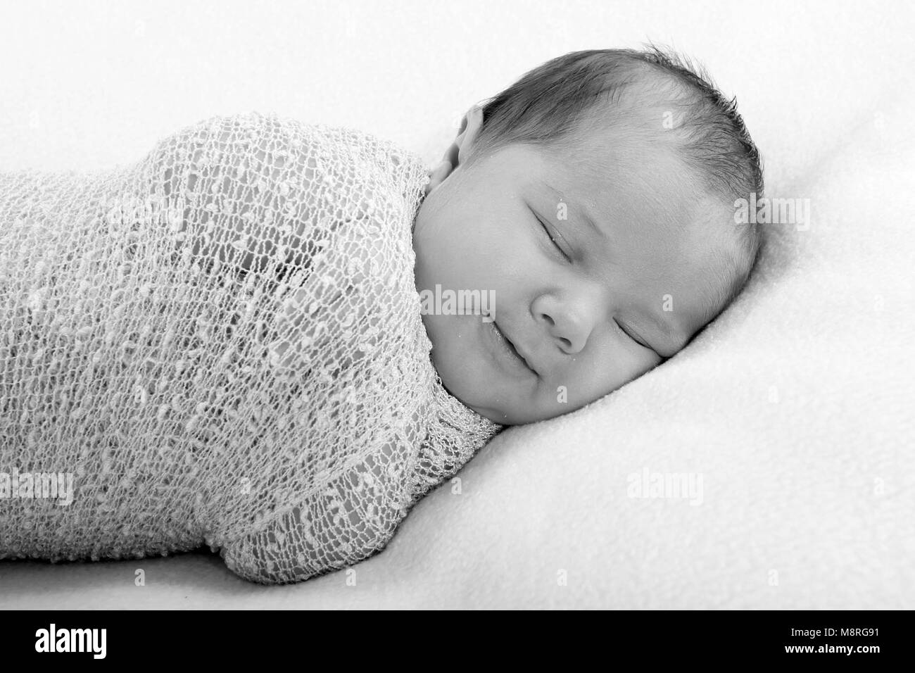 Cutie Newborn Baby Girl In Swaddling Wrap On Soft Blanket In Nursery